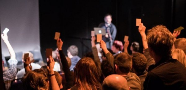 Audience members holding up cards to make choices in Remote